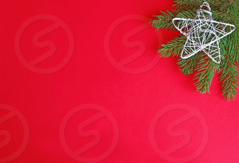 red and green christmas background with a silver colored wire star and a spruce branch photo
