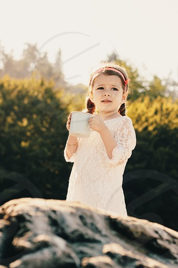 brunette braided hair girl wearing a white lace dress holding a white mug near a grey rock with the sun shining over green trees in the distance photo