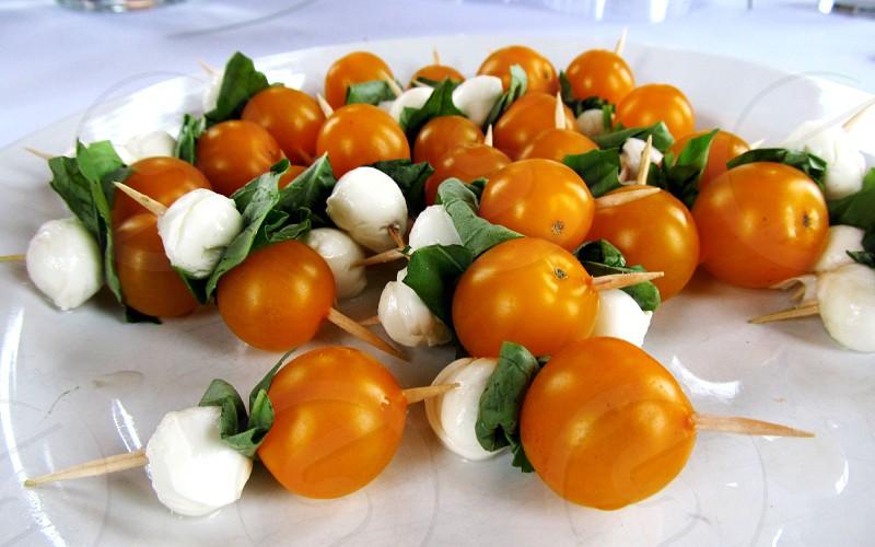 Orange tomatoes mozzarella and fresh basil on toothpicks on white plate photo