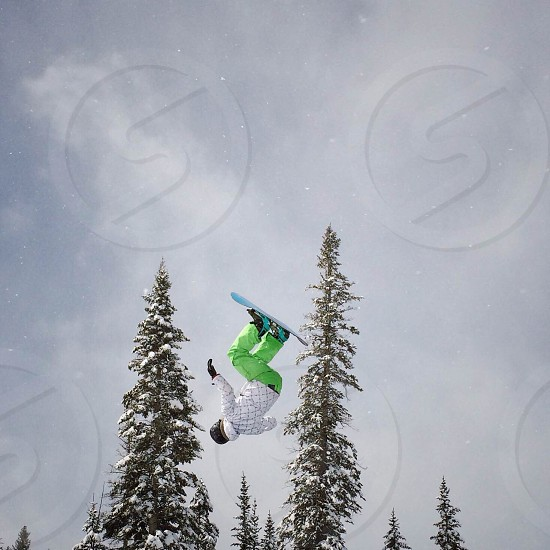 person wearing white coat green pants riding blue snowboard executing an upside down flip photo