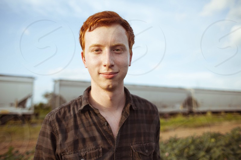 standing smiling red-haired man wearing two-tone brown check button-up shirt photo