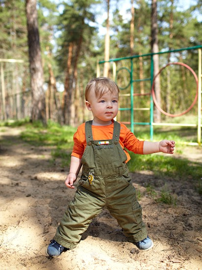 Kid staying alone independently outdoors. Nature forest. photo