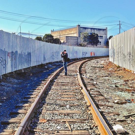 Man on train tracks shooting a photo  photo