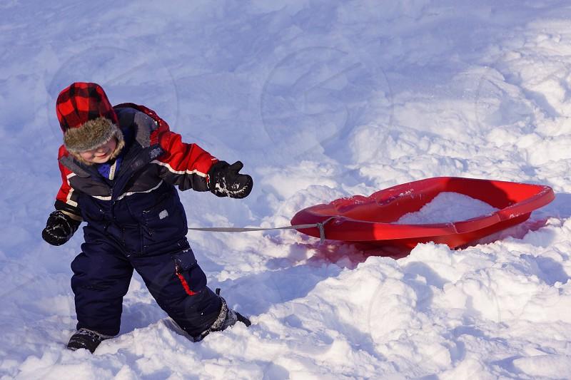 Little boy pulling sled coat hat mittens snow winter photo