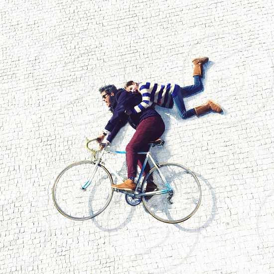 woman holding on man riding bicycle photo