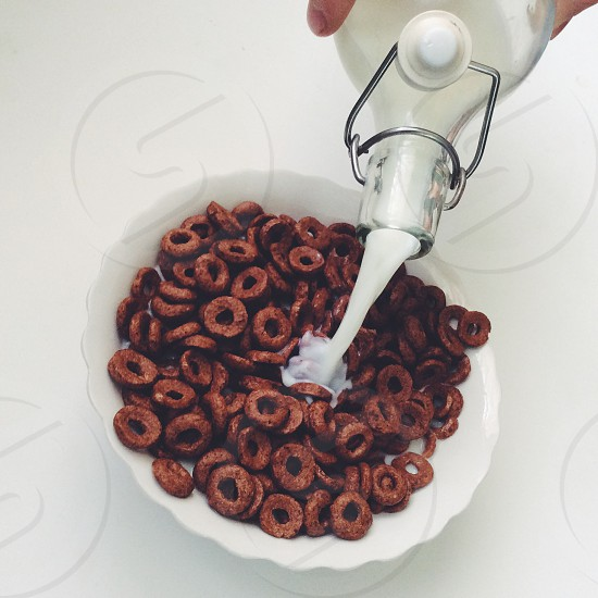 milk being poured into chocolate loops cereal in white round bowl photo