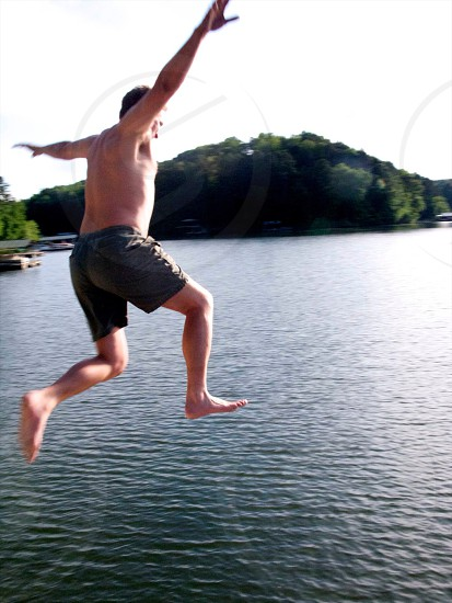 Playful man jumping from dock into lake photo