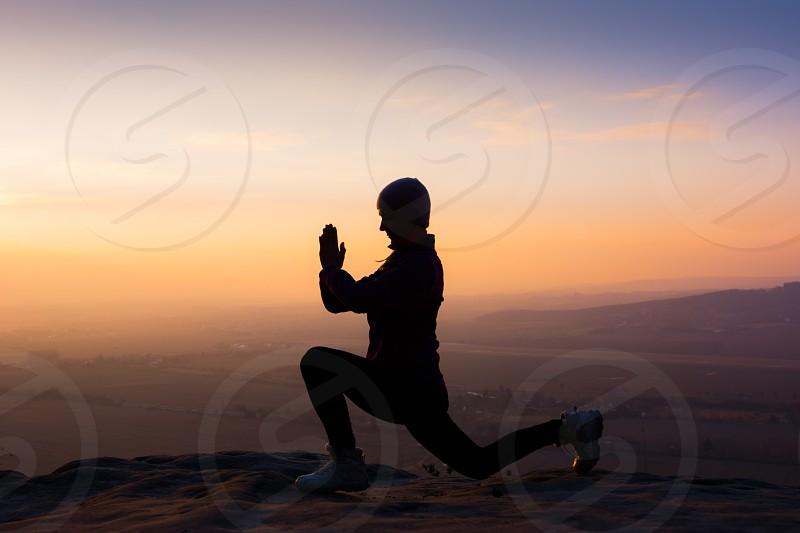 Young fitness woman meditating on sunrise mountain peak. photo