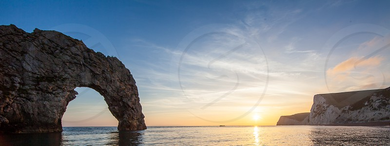 Sunset at Durdle Door on the Jurassic coast of Doset England in the uk featuring a natural geolicaly formed arch over the sea photo
