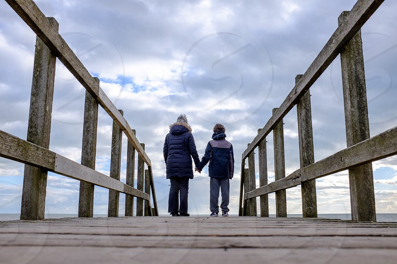 Back view of grandma and grandson wearing winter clothes holding  hands on a fenced walk way looking out to the sea and sky with diminishing perspective photo