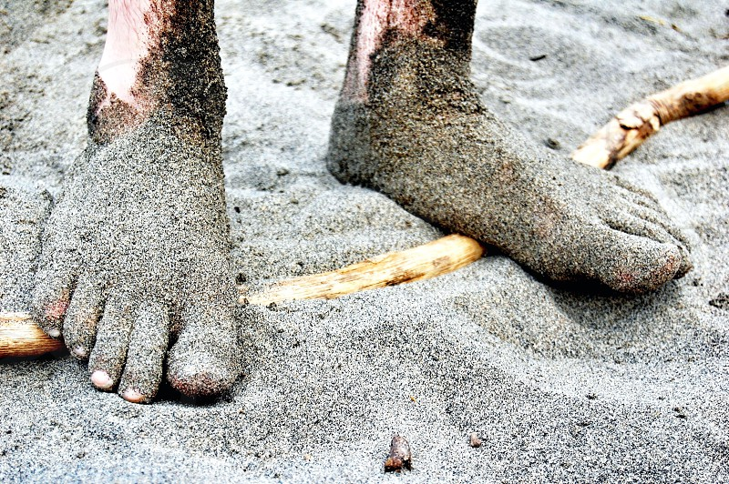 person feet covered in gray sand photo