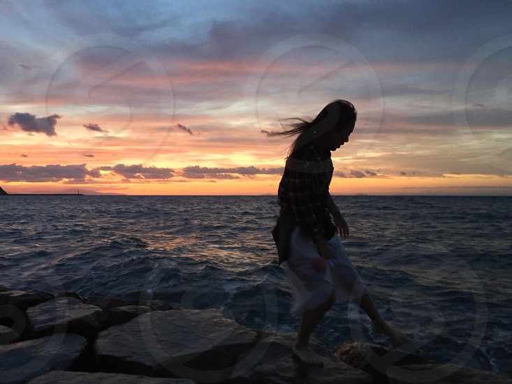 woman standing near body of water during sunset photo