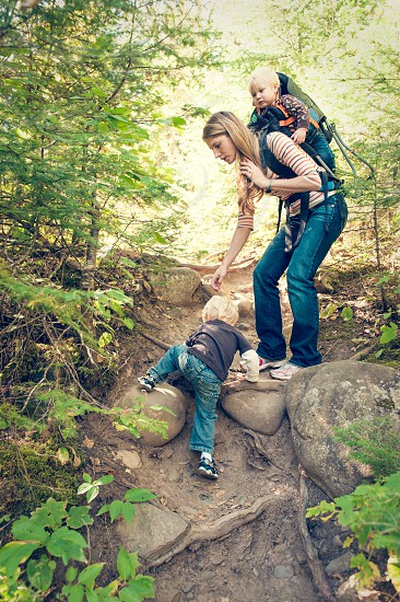 active family backpack hiking mother children boys female hair jeans climb rock trail woods trees forest exercise fun summer walking photo