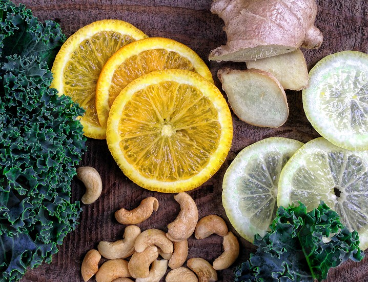 Aerial view of slices of orange lemon with kale cashews and sliced ginger. photo