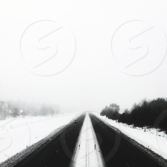 Foggy vanishing winter road in black and white photo