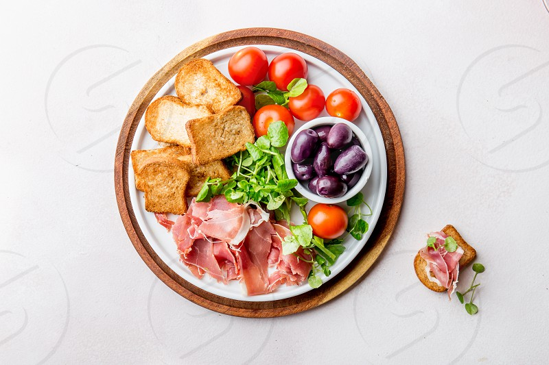 Antipasto Plate with dried bread ham serrano tomato cherry and purple olives. White background photo