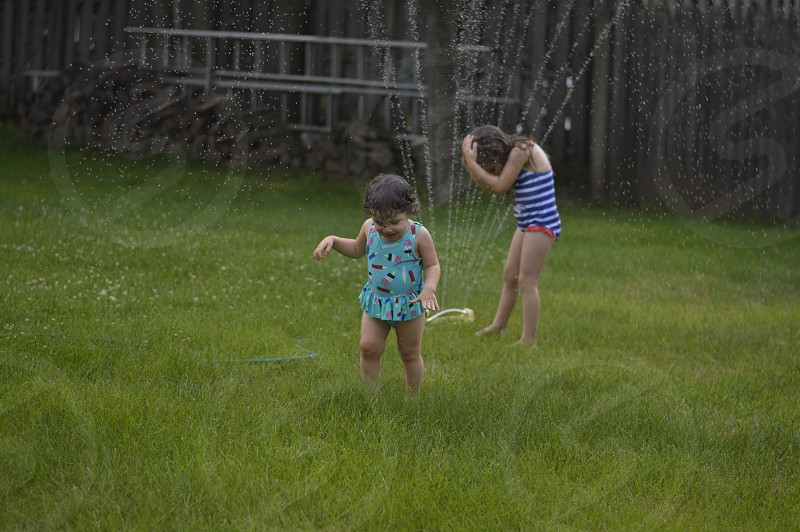Bathing suits ice cream girls sprinkler water hose grass green blue photo