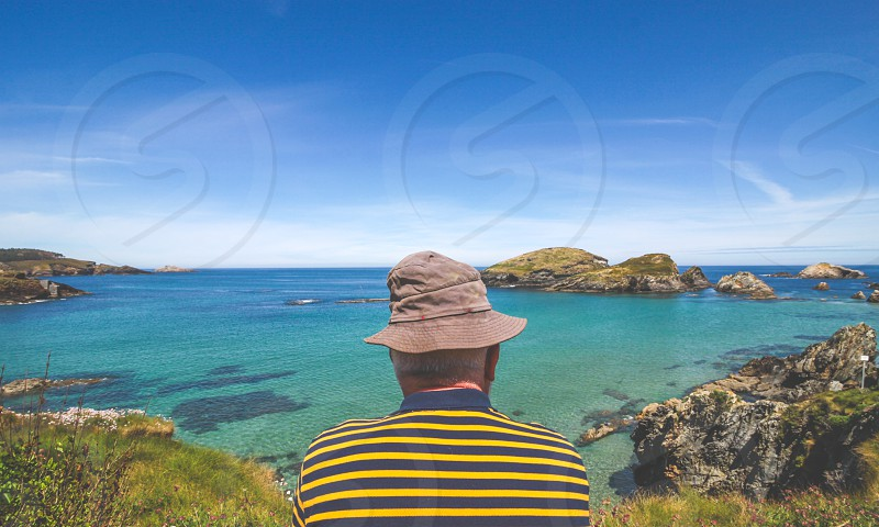 Rear view of a mature man looking the seascape. photo