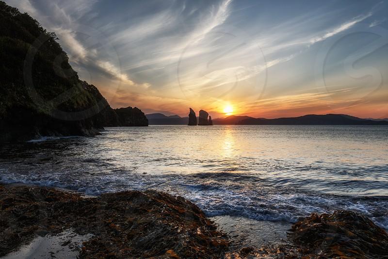 Seascape of Kamchatka Peninsula: beautiful view of sunset over Three Brothers Rocks in Avacha Bay (Pacific Ocean). Kamchatka Region Russia Far East Eurasia. photo