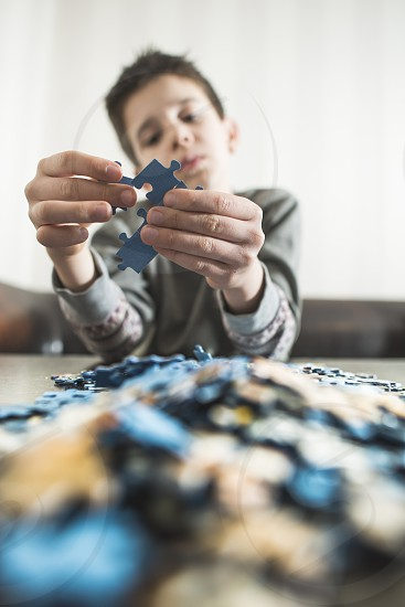 Child and puzzle. Pile puzzles photo