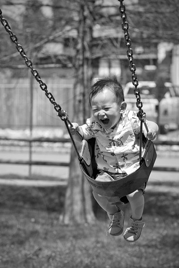 baby playing swing gray scale photography photo