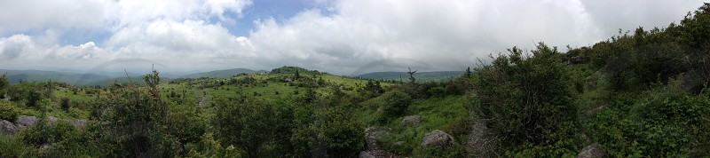 view of white clouds and grassy mountains photo