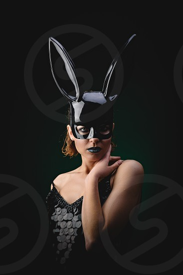 Sexy woman with a Easter bunny black mask standing on a dark background and looks sensually photo