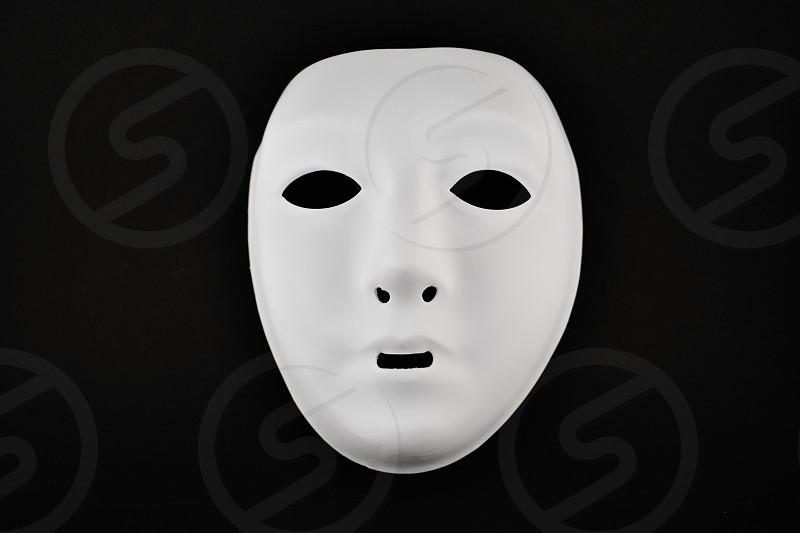 Plastic white face mask. White mask on a black background. Plastic human mask photo