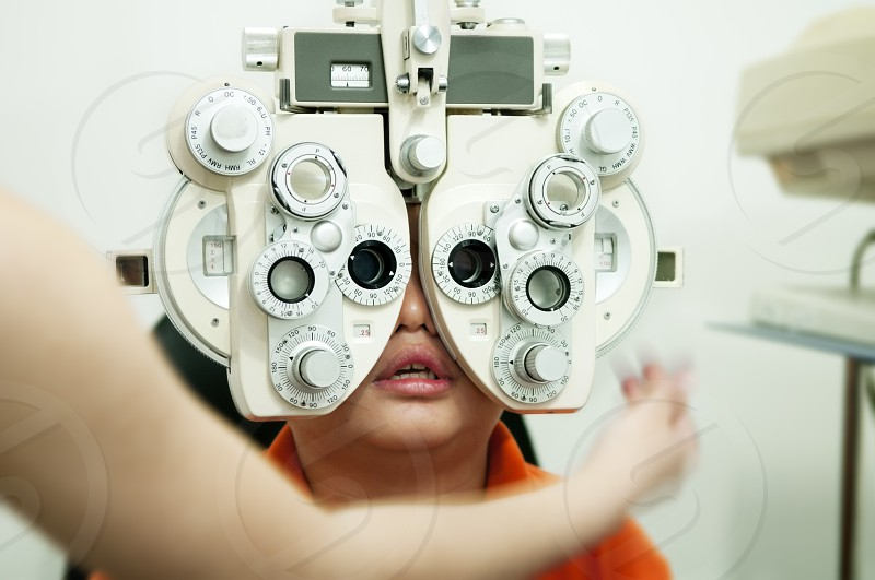 Closeup portrait of a boy undergoing eye test with phoropter photo