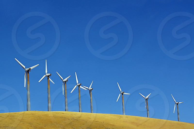 Eight wind turbines stand on top of a hill against a blue sky. photo