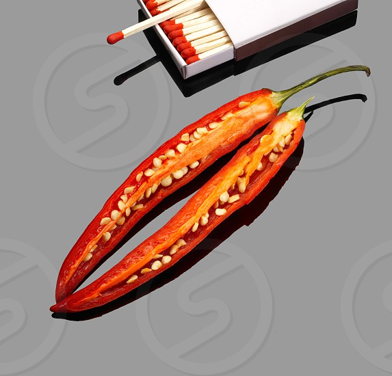 fresh red chili peppers  with matches over grey reflective surface photo