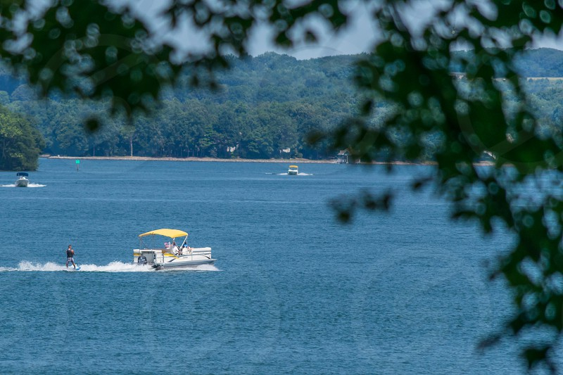 Waterskiing on the lake with a waterboard and a pontoon boat photo