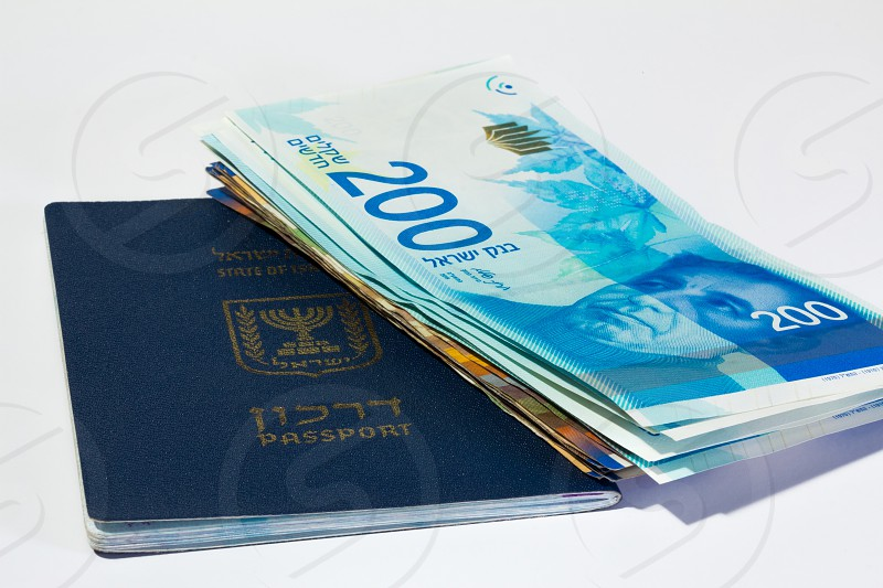 Stack of israeli money bills of 200 shekel and israeli passport. photo
