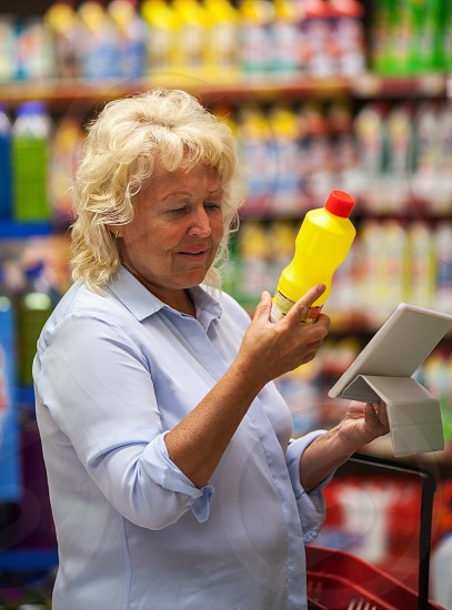 Senior woman choosing detergent in the shop. She checking the bottle label and using tablet computer to be sure with safety of goods photo