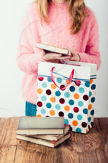 Young girl putting the books into paper bag in bookstore. A few books on a wooden table. Teenager girl wearing pink sweater and blue jeans. Vertical photo photo