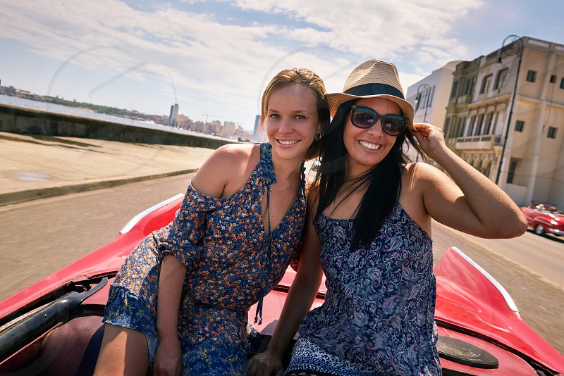 car; happy; women; girls; friends; people; tourists; 20s; beautiful; camera; classic; convertible; couple; cuba; cuban; enjoy; female; friendship; fun; girl; happiness; havana; hispanic; holidays; joy; latina; laughing; looking; looking at camera; old; portrait; pretty; sea; smile; smiling; summer; tourism; tourist; transportation; travel; travelers; traveling; trip; two; vacations; vehicle; vintage; woman; young photo