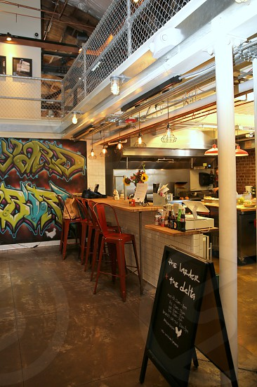 shop with red bar stools in front of white and brown bar counter with sunflower in a base near wall with graffiti photo