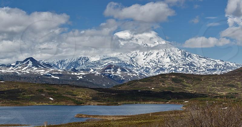 Panorama: beautiful mountain (volcanic) landscape of Kamchatka Peninsula: view of active Ichinsky Volcano and mountain lake. Russia Far East. photo