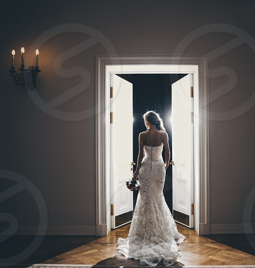 the bride is alone in a white dress with a train with a bouquet photo