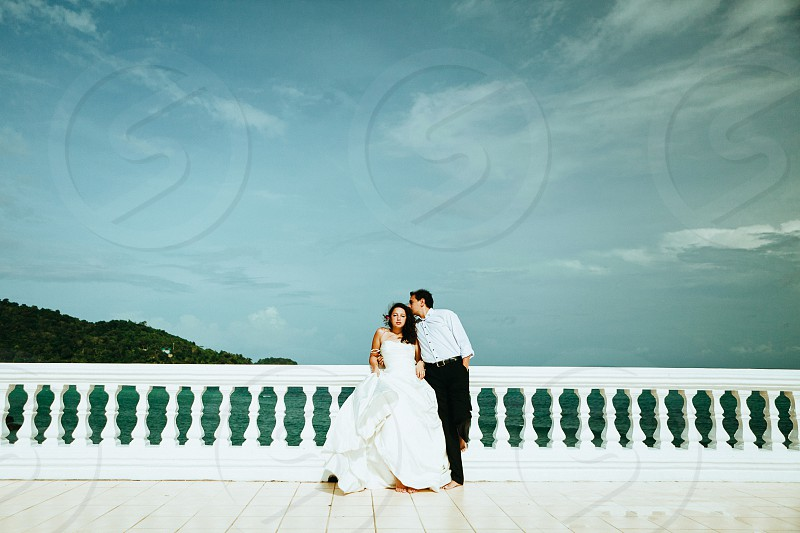 Bride and groom standing on terrace photo
