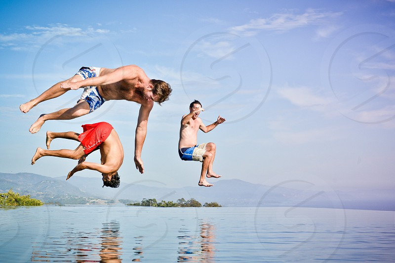 3 men jumping into body of water photo
