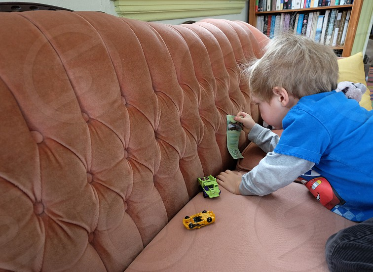A little boy finding a Canadian 20 dollar bill in the couch photo