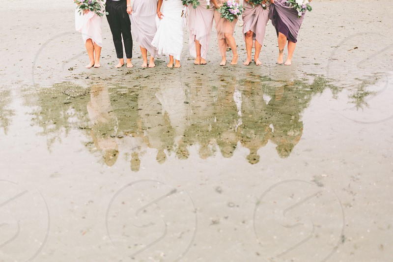 A bridal party standing at the edge of a tidal pool looking at their reflections.  photo