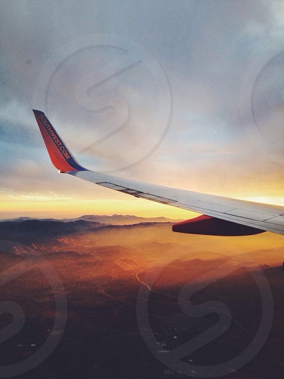 Wing of Southwest Airlines airplane with mountains clouds and sunset in the background.  photo