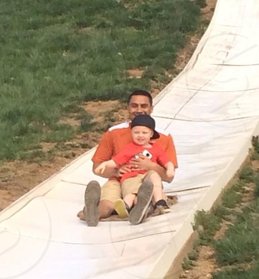 photo of man holding boy on slide photo