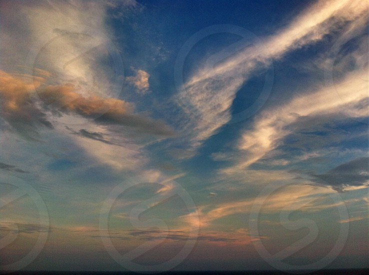 blue sky with wispy clouds at sunset photo