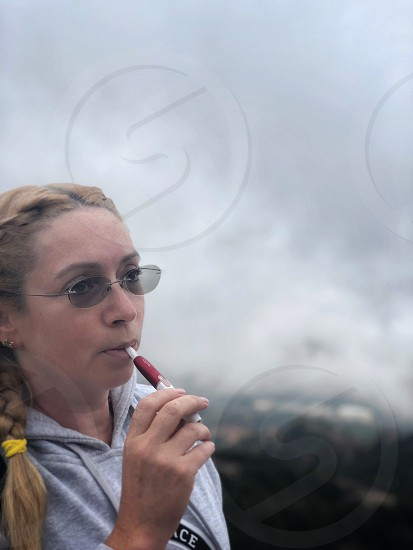 Young woman in glasses smokes electronic cigarette IQOS on a cloudy foggy day.  photo
