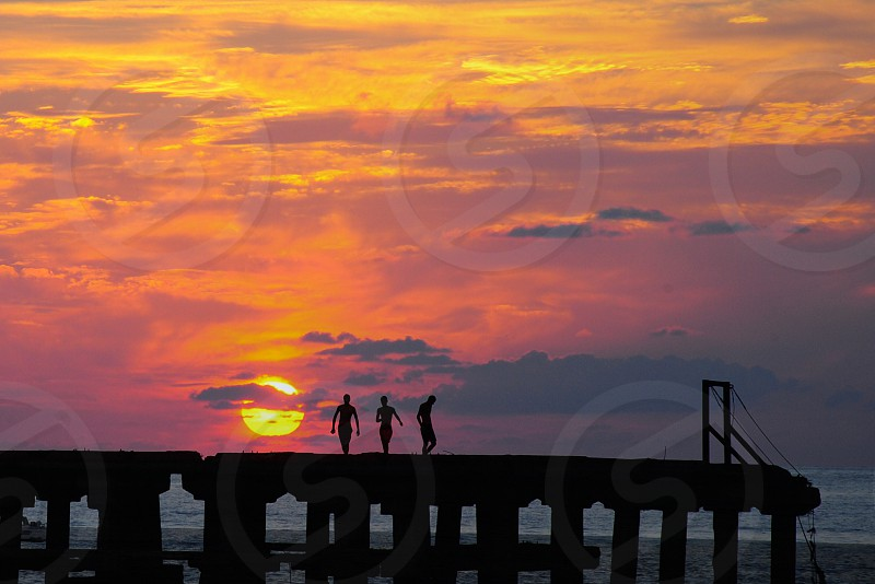 3 people on concrete dock silhouette under sunset view photo