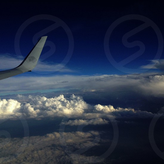 white commercial plane on top of the clouds photo