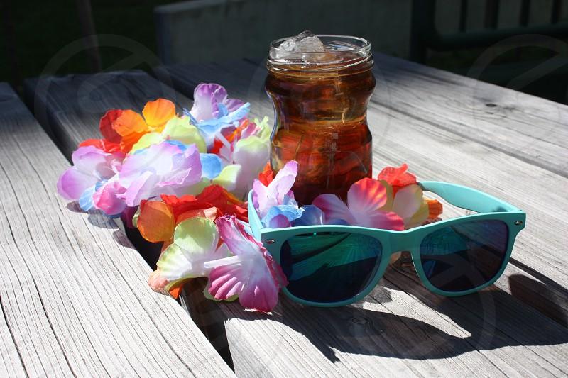 ice tea sunglasses flower girland wooden table photo